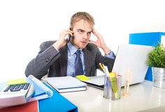 Young businessman worried tired talking on mobile phone in office suffering stress Stock Image