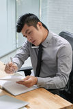 Young businessman wrapped up in work Stock Photos