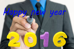Young businessman write words Happy New Year. Young businessman write a greeting Happy New Year stock photography