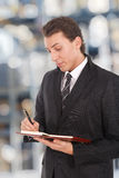 Young businessman writing. Something on his agenda. Blurred background Stock Photography