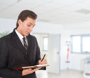 Young businessman writing. On his agenda in an office environment Stock Images
