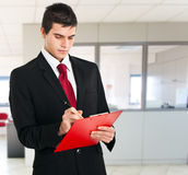 Young businessman writing. On his agenda in an office environmant Stock Photo