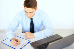 Young businessman writing on clipboard. At his workplace in bright office Stock Photos