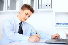 Young businessman writing on clipboard. At his workplace in bright office Royalty Free Stock Photography