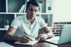 Young Businessman Writing Notes and Using Laptop. Stock Photography