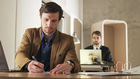 Young Businessman Writing on a Piece of Paper. Two career people in the office. Medium shot. Shot on RED Epic stock video footage