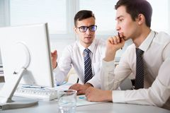 Young businessmen discussing a project. Young businessmen discussing new project at meeting Royalty Free Stock Image