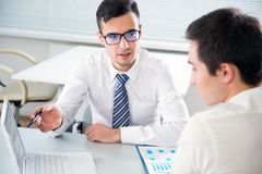 Young businessmen discussing a project. Young businessmen discussing a new project at modern office Royalty Free Stock Images