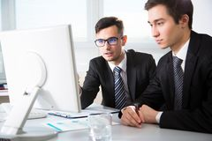 Young businessmen discussing a project. Young businessmen discussing a new project at modern office Royalty Free Stock Image