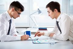 Young businessmen discussing a project. Young businessmen discussing a new project at modern office Stock Image
