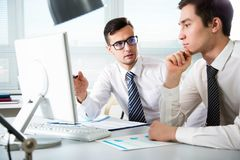 Young businessmen discussing a project. Young businessmen discussing a new project at modern office Stock Photo