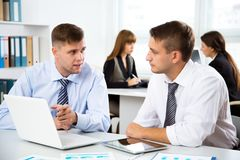 Young businessmen discussing a project. With laptop at modern office Stock Image