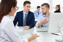 Young businessmen discussing a project. With laptop at modern office Royalty Free Stock Photography