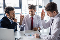 Young businessmen in formal wear discussing business charts and showing ok sign Royalty Free Stock Photo