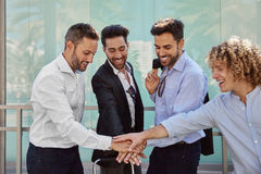 Young businessmen holding hands together in unity gesture Royalty Free Stock Images