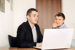 Young Businessmen Looking at Laptop on Table. Two Sitting Young Businessmen Looking Something at Laptop on Table at the Office Stock Photos