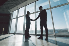 Young businessmen are shaking hands with each other standing against panoramic windows. Two young businessmen are shaking hands with each other standing against royalty free stock photos