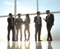 People walk in the office on the sunny background. Young businessmen are standing in modern office with panoramic windows royalty free stock image