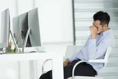 Young businessmen in stress. Sit in front of modern office computer, concept for hard work in an organization. stock image