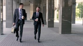 Young businessmen talking to each other and drinking coffee. Before the working day stock footage