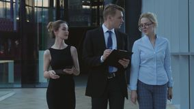 The young businessmen team goes to the meeting. This footage illustrates successful team, cooperation and partnership, business meeting in a big company stock footage