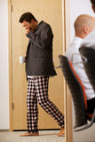 Young businessmen walkin across the corridor with pijamas pants Royalty Free Stock Images