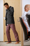 Young businessmen walkin across the corridor with pijamas pants Royalty Free Stock Photos