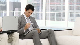 Young businessmen working. Sitting on a sofa stock footage