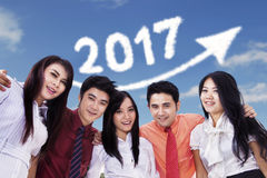 Young businesspeople with arrow and 2017. Group of young businesspeople smiling at the camera with upward arrow and number 2017 on the sky Royalty Free Stock Images