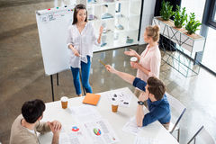 Young businesspeople discussing charts at workplace Stock Photography