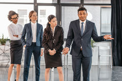 Young businesspeople in formalwear posing while standing at modern office. Multicultural business team Royalty Free Stock Photos