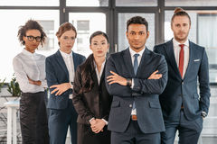 Young businesspeople in formalwear posing while standing at modern office. Multicultural business team Stock Photo