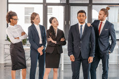 Young businesspeople in formalwear posing while standing at modern office. Multicultural business team Royalty Free Stock Image
