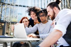 Young businesspeople with laptop in courtyard, start-up concept. Young businesspeople with laptop outdoors in courtyard, laughing. Start-up concept royalty free stock photo