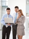 Young businesspeople looking at laptop screen. Young businesspeople standing in office lobby, holding laptop, looking at screen royalty free stock photo