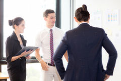 Young businesspeople pointing towards graph with present profit Royalty Free Stock Photography