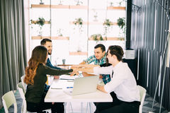 Young businesspeople putting hands together on the table at the office meeting Stock Photos