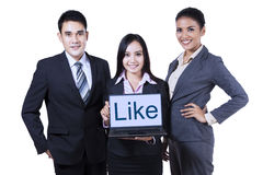 Young businesspeople showing like on laptop. Group of asian business people showing like on laptop at office royalty free stock image