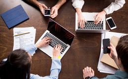 Young businesspeople sitting together at workplace and using digital devices. Overhead view of young businesspeople sitting together at workplace and using Stock Photos