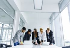 Young businesspeople stand in the office and analyze business re. Young businesspeople stand in the office and analyze together business results royalty free stock images