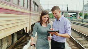 Young businesspeople use a tablet at a railway station. A train passes by. Technology in Travel stock video footage
