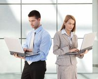 Young businesspeople using laptop in office lobby royalty free stock photos