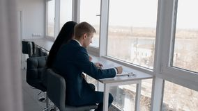 Young businesspeople working on business project sitting by window in modern office. Young businesspeople working on business project sitting by window in stock footage