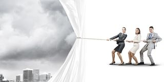 Young businesspeople working in collaboration and pulling white advertisement banner Stock Image