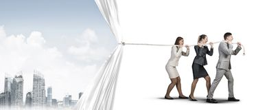 Young businesspeople working in collaboration and pulling white advertisement banner Stock Photo