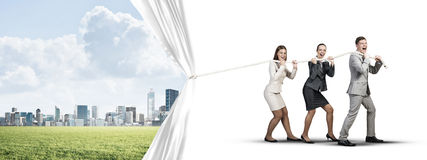 Young businesspeople working in collaboration and pulling white advertisement banner Royalty Free Stock Images