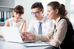 Young businesspeople working with laptop. In office Stock Photos