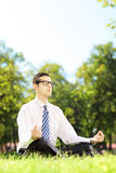 Young businessperson with eyeglasses meditating seated on a gras Stock Image