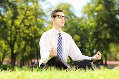 Young businessperson with eyeglasses meditating seated on a gras Stock Photos
