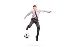 Young businessperson kicking a football Royalty Free Stock Photography